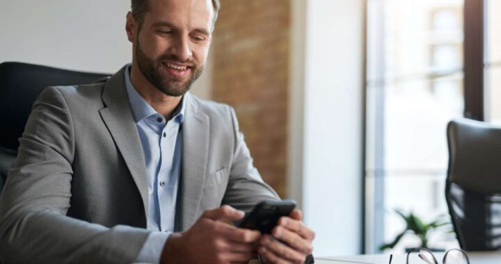 Gladsome handsome man in a suit looking at the screen of smartphone with a smile while sitting at the table