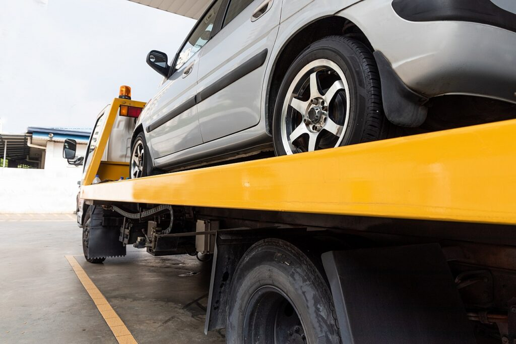 broken-car-on-flatbed-tow-truck-being-transported--UA2Y3P5